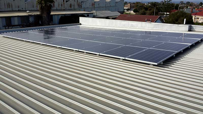 Discrete solar panel installation on flat roof